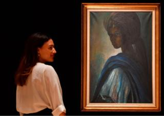 An worker poses with a work of art by Nigerian painter and sculptor Ben Enwonwu entitled 'Tutu' approaching to realize 200,000-300,000 GBP (278000-417,000 USD) during auction in Bonhams auction residence London on Feb 7, 2018. Tutu, a recently rediscovered mural of a Ife stately princess Adetutu Ademiluyi embellished in 1974 by a Nigerian artist Ben Enwonwu, leads Bonhams Africa Now sale in London on Feb 28. The painting, one of a array of 3 versions, once suspicion mislaid came to light after carrying left secret for decades in a north London flat. The locale of a other dual versions stays a mystery.