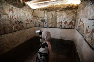 A lady takes a print inside a tomb of an Old Kingdom priestess ornate with well-preserved and singular wall paintings on a Giza plateau in Cairo that was denounced on Feb 3, 2018 after being detected during cave work in Giza's western tomb by a group of Egyptian archaeologists. Antiquities Minister Khaled al-Enany told reporters a tomb go to Hatpet, a priestess to Hathor, a enchantress of flood who assisted women in childbirth.