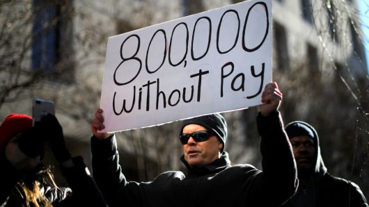 A malcontent binds a sign, signifying hundreds of thousands of sovereign employees who won't be receiving their paychecks as a outcome of a prejudiced supervision shutdown, during a Rally to End a Shutdown in Washington, Jan 10, 2019.