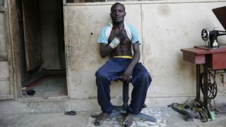 A proffer vigilante sits outward his residence after a quarrel opposite Boko Haram