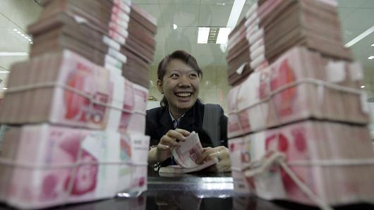 A clerk depends stacks of Chinese yuan during a bank in Beijing, China.