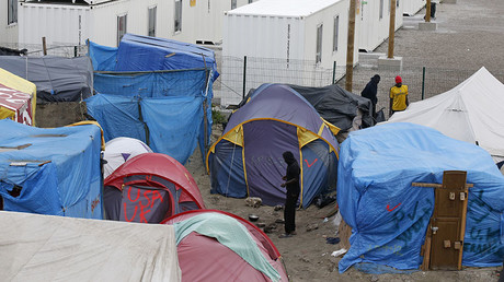 Migrants mount adult outward their shelters in a northern area of a stay called a