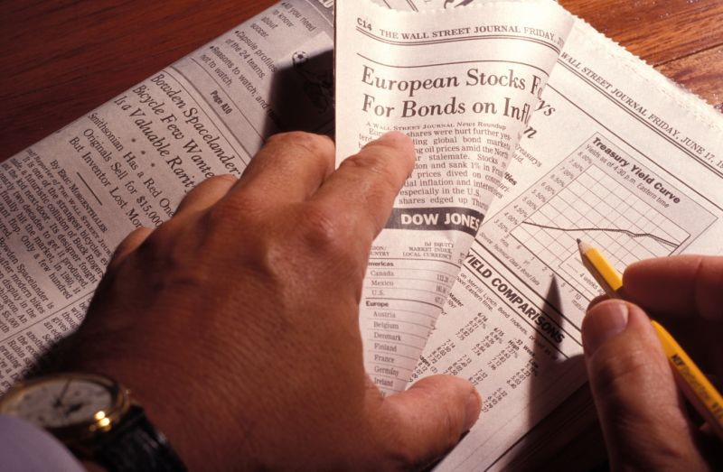 Hands Holding Financial Section Of Newspaper, Following Treasury Yield Curve. (Photo by Education Images/Universal Images Group around Getty Images)