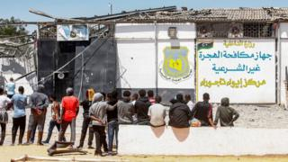 Migrants mount outward a apprehension centre used by a Libyan Government in a collateral Tripoli