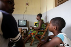 Jean-Noel Kouame joins his family as they watch radio inside their residence in Abidjan, Ivory Coast, Dec. 18, 2017.
