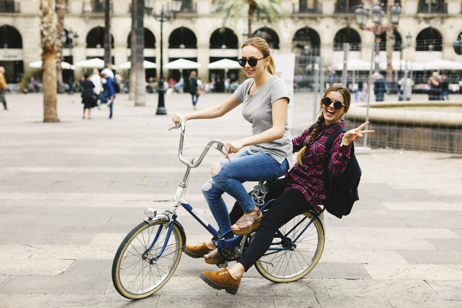 Two immature women cycling on one bike