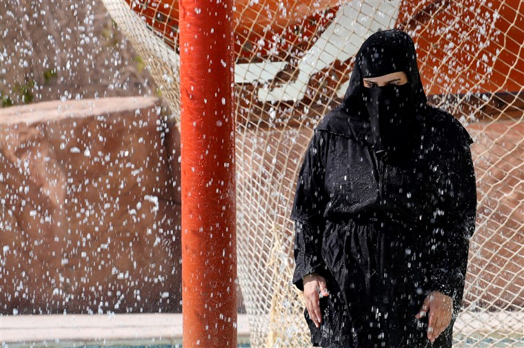 Image: A lady wearing a full deceive (niqab) uses a showering to cold off in prohibited and wet continue inside an Aqua locus during summer holidays during El Ain El Sokhna in Suez, easterly of Cairo