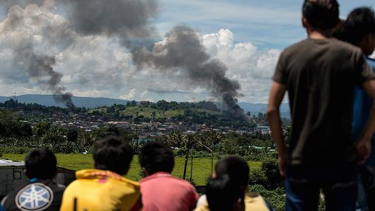 People watch as fume billows from houses after aerial bombings by Philippine Airforce planes on Islamist belligerent positions in Marawi on a southern island of Mindanao on Jun 17, 2017. Philippine infantry have been pulsation militants holding tools of Marawi City with atmosphere strikes and artillery. The genocide fee has risen to some-more than 300 after scarcely a month of fighting.