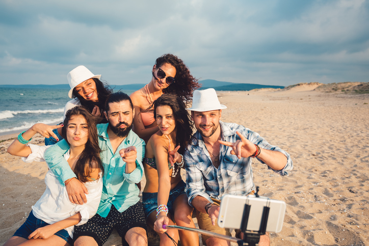 Friends during a beach holding selfie
