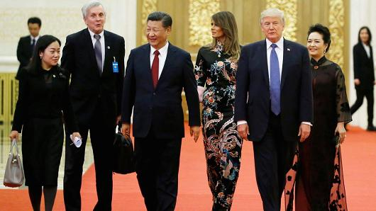 The troops help carrying a arch football (second from left) with U.S. President Donald Trump and China's President Xi Jinping during Beijing's Great Hall of a People.