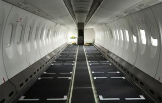 An inside perspective of an dull aeroplane nude of a seats.
