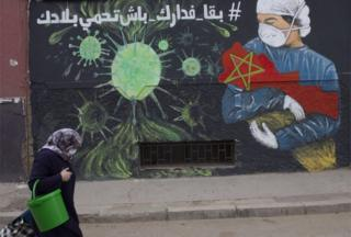 A lady wearing a facade walks past a vast picture depicting a masked health workman cradling a republic of Morocco in their arms.