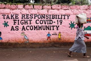 A lady walks past a picture whose aphorism reads: Take responsibility, quarrel opposite Covid-19 as a community.