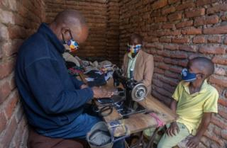 Two masked people demeanour on as a tailor creates face masks.