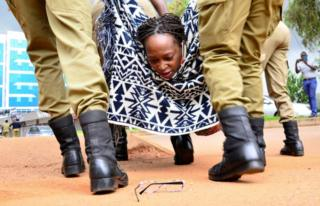 A lady looks behind during her eyeglasses as she is forcibly carried divided by uniformed officers.
