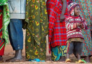 A child wearing a knitted shawl and jumper stands subsequent to a line of adults wearing garments in several patterns.