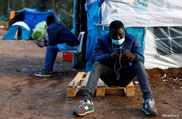 Two migrants are photographed together in a tents where they have lived for weeks in La Laguna, on a island of Tenerife.