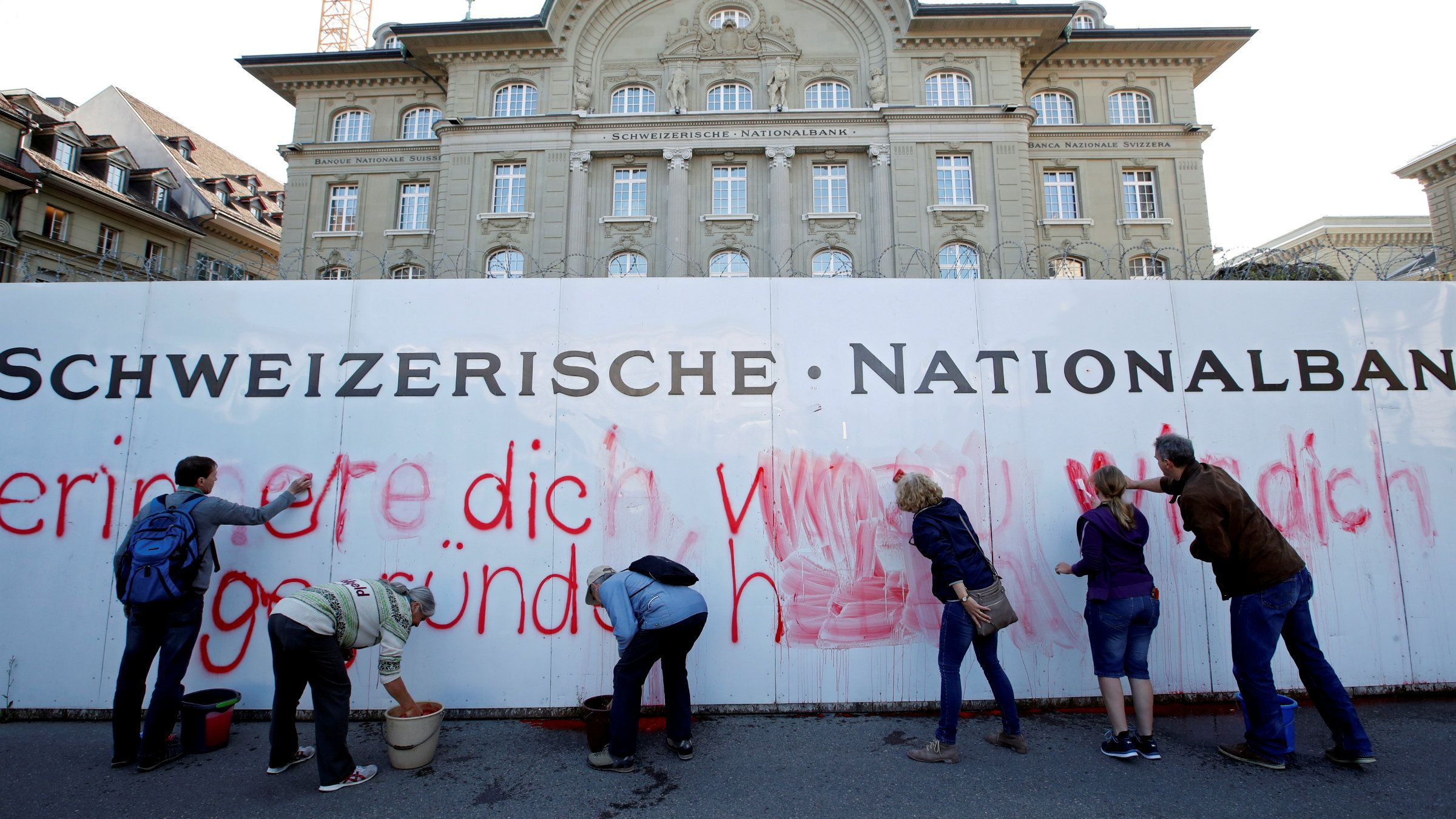 Supporters of a emperor income beginning paint a aphorism on a wall outward a Swiss National Bank
