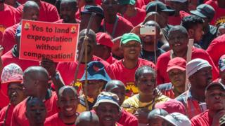A malcontent in South Africa binds a poster reading Yes to land sequestration though remuneration as thousands of workers take partial in a inhabitant strike called by a country's second largest work kinship - Apr 2018