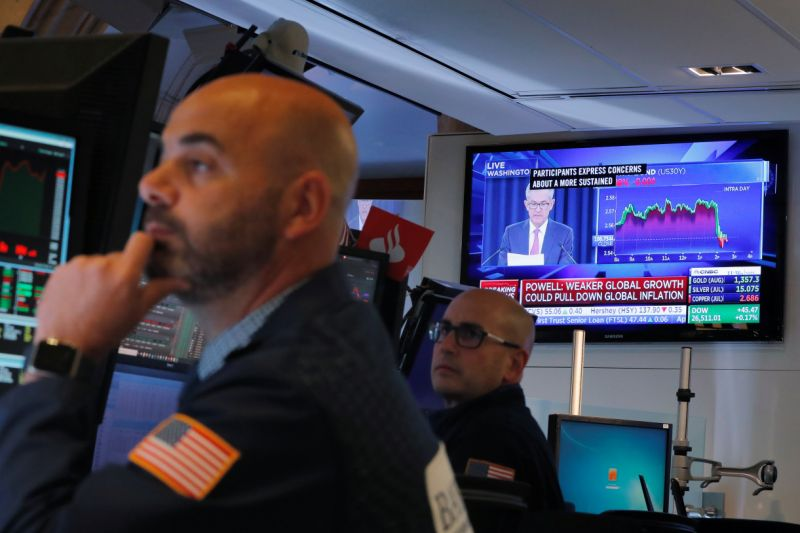 Traders work on a building of a New York Stock Exchange as Federal Reserve Chairman Jerome Powell binds a news discussion on a radio behind them in New York, U.S., Jun 19, 2019. REUTERS/Lucas Jackson