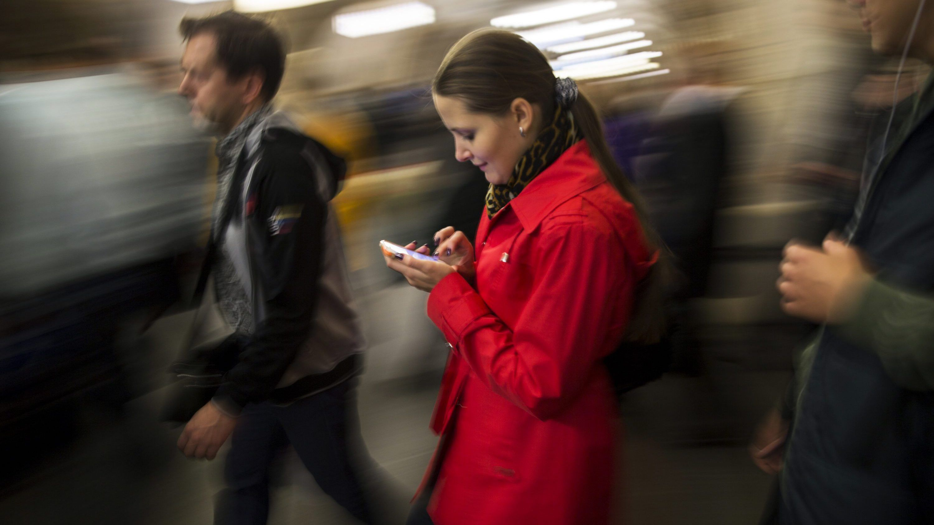 A lady surfs a Internet on her smartphone in Moscow's subway, Russia, Tuesday, Sept. 16, 2014.
