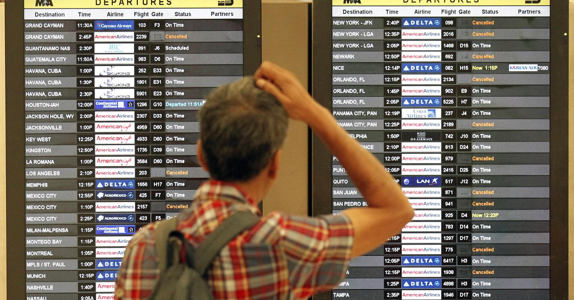 A newcomer checks a depart house as flights during Miami International Airport are canceled.