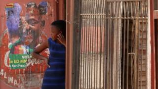 A lady looks on subsequent to a defaced debate print of President Emmerson Mnangagwa in Harare, Zimbabwe - Monday 6 Aug 2018