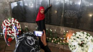 A Kenyan lady (C), who mislaid her relative, poses for a print being taken by her crony as she stands in front of a board temperament a names of those killed during a 1998 bombing of US Embassy, during a Aug 7th commemorative park in Nairobi, Kenya, 07 Aug 2018.