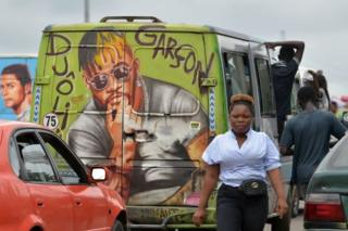 People and cars are seen on a highway subsequent to a minibus embellished with a mural of DJ Arafat.