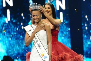 Zozibini Tunzi smiles and clutches her chest as a winner's tiara is laid on her head.