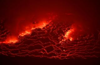 Molten lava cracks and froth red.