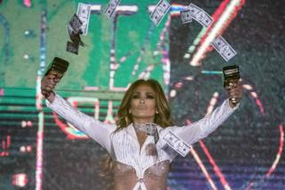 Jennifer Lopez binds a span of income gun aloft and sprays a records into a air.