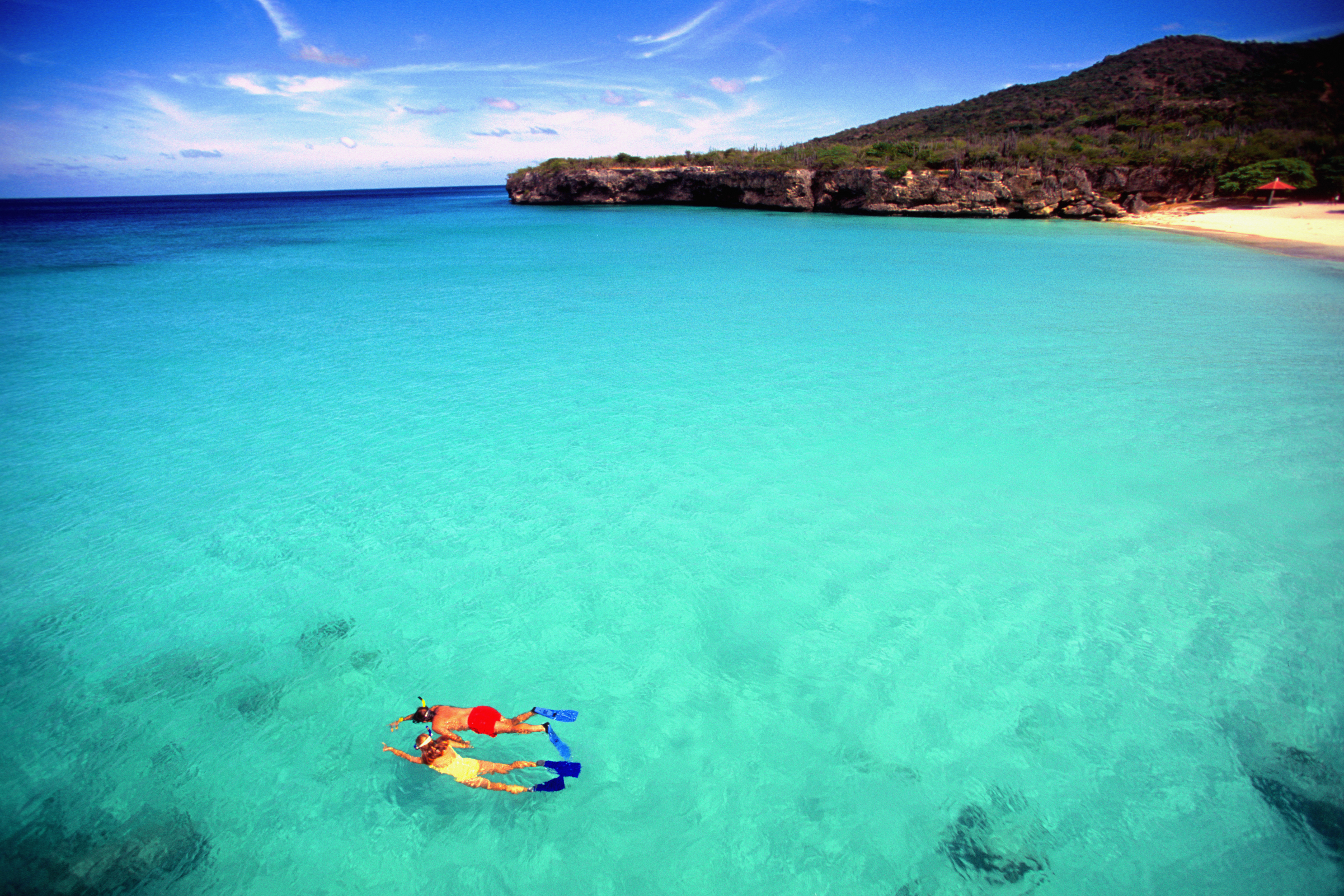 Couple snorkeling in transparent transparent H2O off Knip Beach in Curacao.