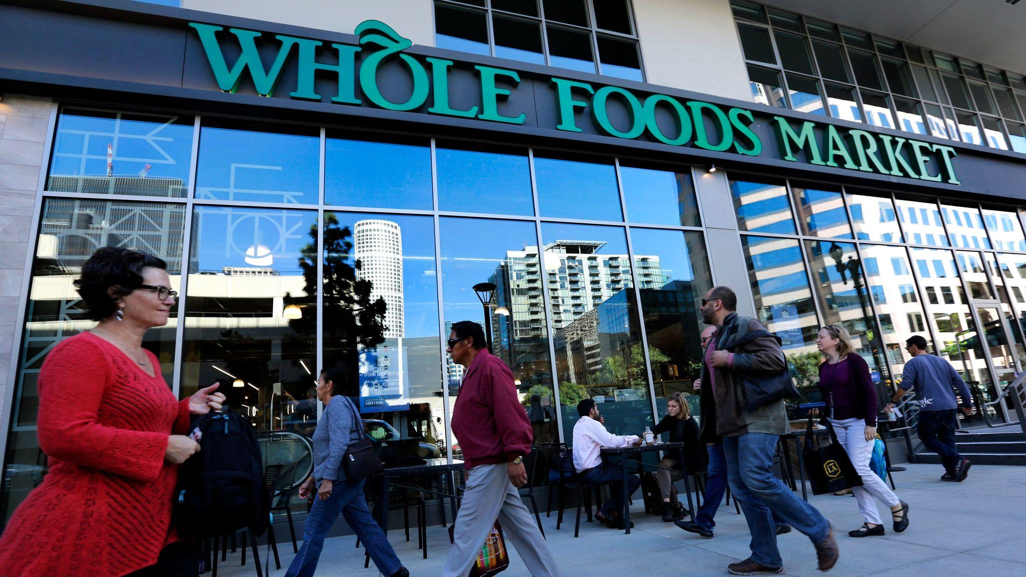Pedestrians make their approach past a Whole Foods Market on Grand Avenue in downtown Los Angeles during a store's grand opening on Dec 4, 2015.