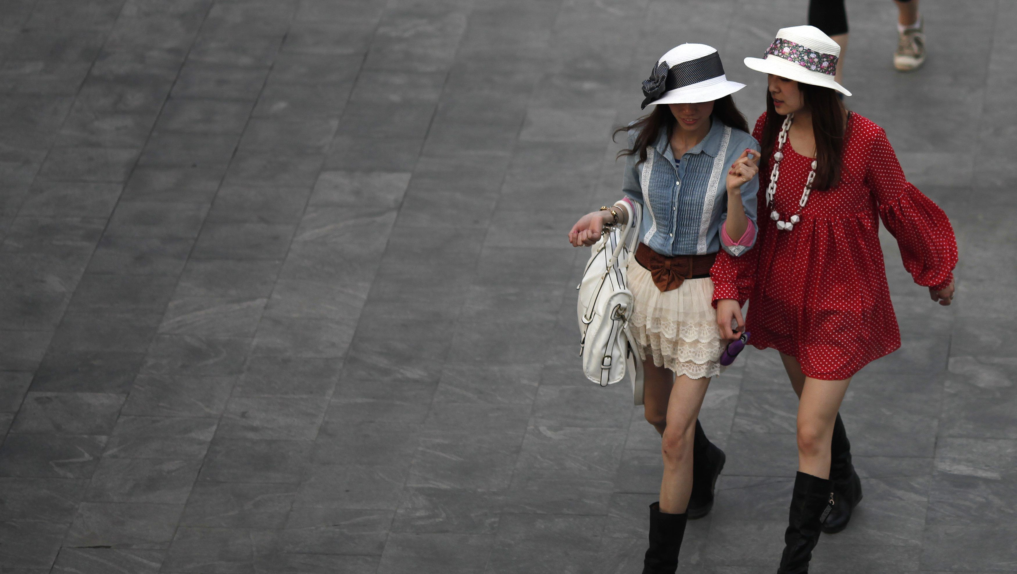 Women travel in a financial area of Pudong in Shanghai Apr 26, 2011.