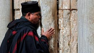A Christian Ethiopian clergyman prays subsequent to a sealed doorway of a categorical opening of a Church of a Holy Sepulchre in a Old City of Jerusalem on Feb 26, 2018 after Christian leaders took a singular step of shutting a church, seen as a holiest site in Christianity, a prior day during noon