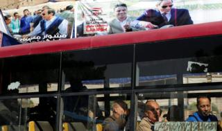 People demeanour out of a train window in front of posters of Egypts President Abdel Fattah al-Sisi for a arriving presidential choosing in Cairo, Egypt Feb 28, 2018