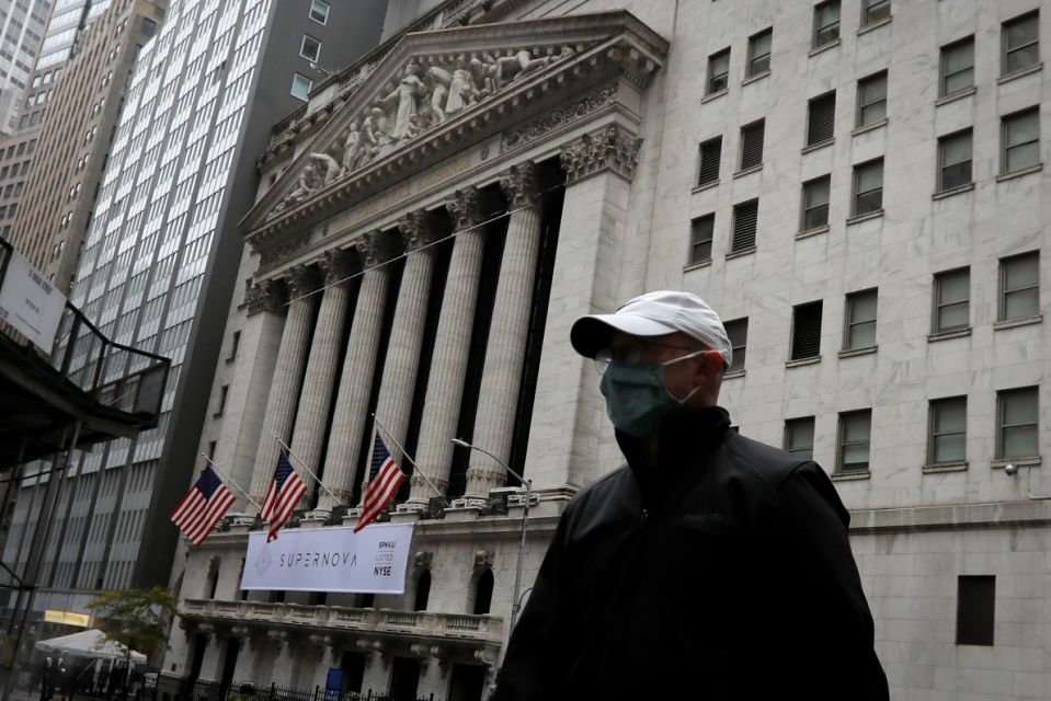 A male wearing a protecting face facade walks past a New York Stock Exchange in Manhattan in New York City, New York, U.S., Oct 26, 2020. REUTERS/Mike Segar