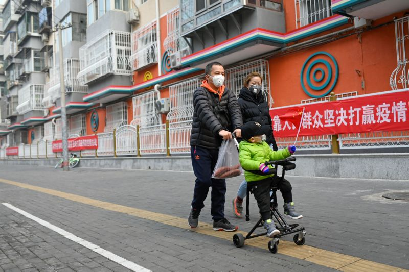 A child wearing a face facade waves a Chinese inhabitant dwindle as he sits on a hiker in Beijing on Feb 13, 2020. - The series of deaths and new cases from China's COVID-19 coronavirus conflict peaked dramatically on Feb 13 after authorities altered a approach they count infections in a pierce that will expected fuel conjecture that a astringency of a conflict has been under-reported. (Photo by STR / AFP) (Photo by STR/AFP around Getty Images)