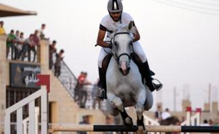 A supplement on his equine jumps over a separator during a Knights of Libya Festival in Benghazi, Libya - Tuesday 7 Aug 2018