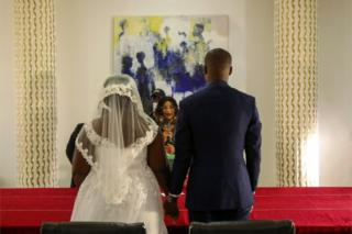 A integrate dressed in marriage attire reason hands as a officiant stands before them.