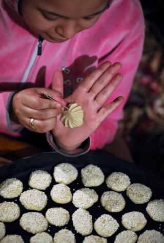 A lady uses a pin-like exercise to make musical settlement on a tiny fritter before it goes in an oven.