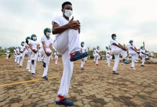 Dozens of masked masculine and womanlike health workers mount in arrangement as they widen in sync.