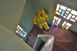 A masculine wearing a yellow PPE fit sprays mosque stairwell that is bright by phony potion windows.