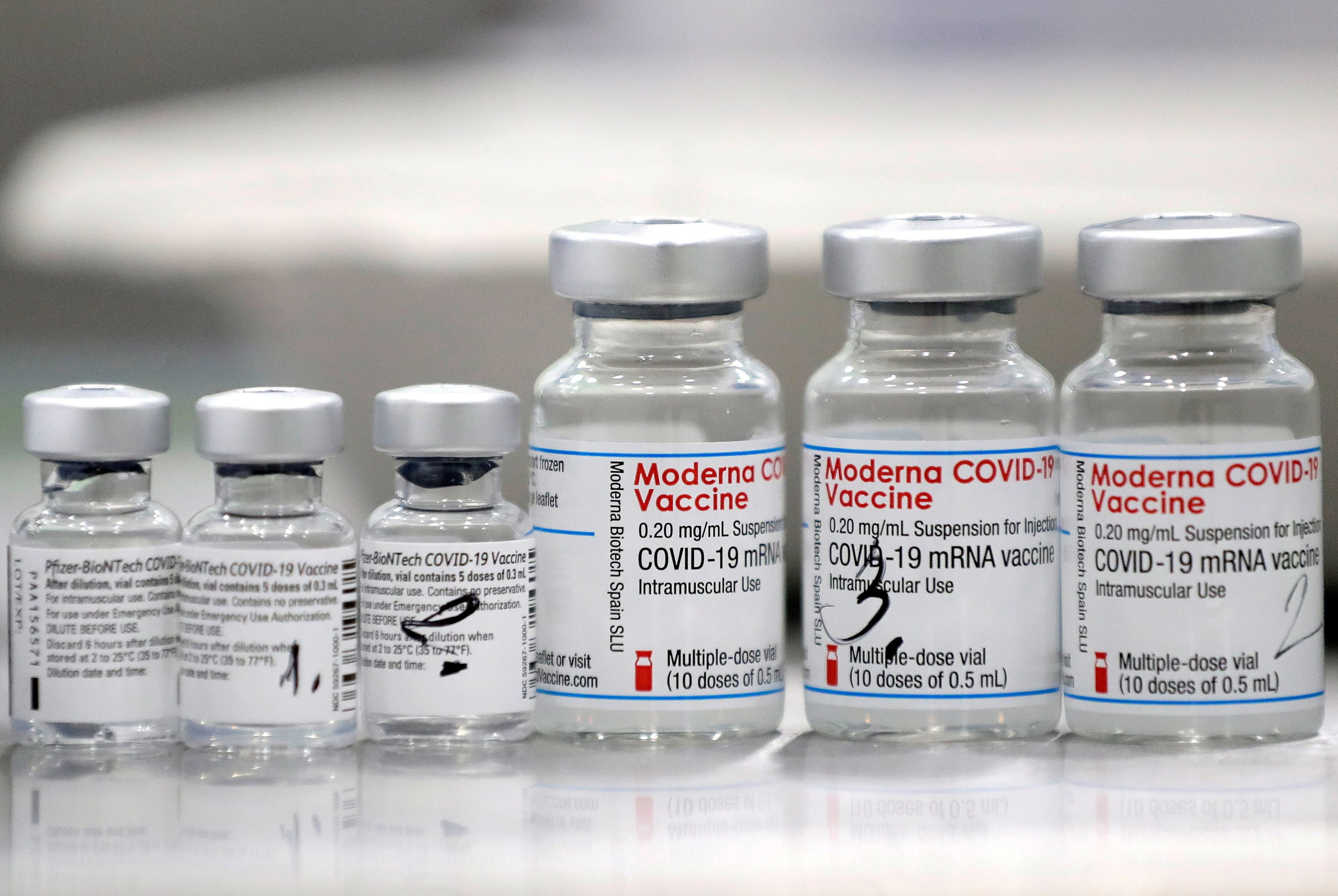 Vials of coronavirus illness (COVID-19) vaccines of Pfizer-BioNTech and Moderna are seen in a city of Ricany nearby Prague, Czech Republic, Feb 25, 2021.  REUTERS/David W Cerny/File Photo