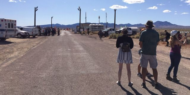 Onlookers take photos of a outward of a behind embankment to Area 51 as onlookers demeanour on.