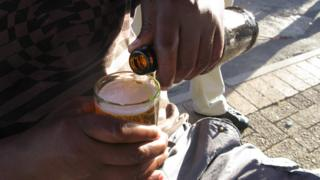 A male pouring a splash during a shebeen in South Africa