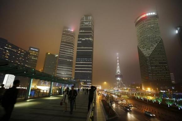 People walk at the financial district of Pudong before Earth Hour in Shanghai