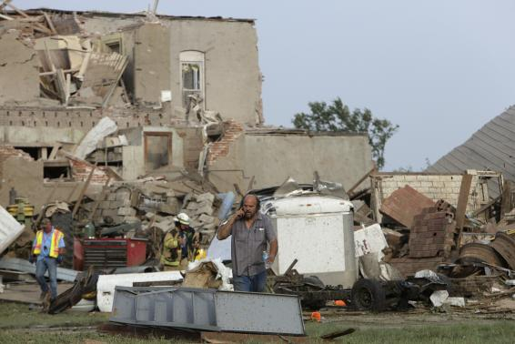 A man talks on the phone in front of tornado-damaged buildings in Pilger, Nebraska